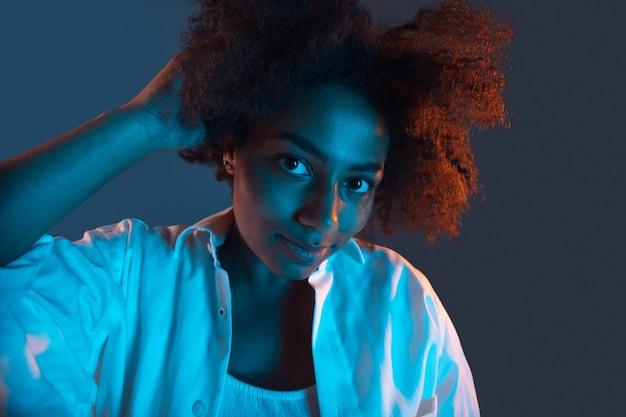 Portret młodej afrykańskiej dziewczyny na czarno-błękitnym w różowym neonowym świetle