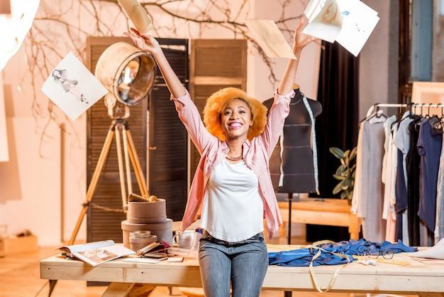 Portret młodej afrykańskiej kreatywnej projektantki mody rzucającej rysunkami w piękne wnętrze studia