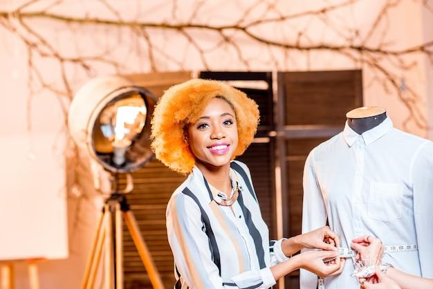 Portret młodej afrykańskiej projektantki mody pracującej z manekinem w studio