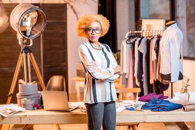 Portret młodej afrykańskiej projektantki mody stojącej w biurze z różnymi narzędziami krawieckimi i ubraniami
