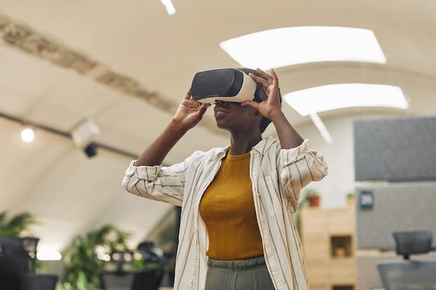Portret młodej afrykańsko-amerykańskiej kobiety w biurze, noszącej sprzęt vr w biurze i cieszącej się wciągającą rzeczywistością, kopiuj przestrzeń