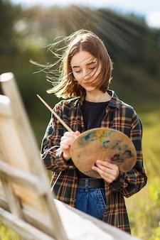 Portret młodej artystki kobiety mieszania farby na palecie w słoneczny letni wieczór