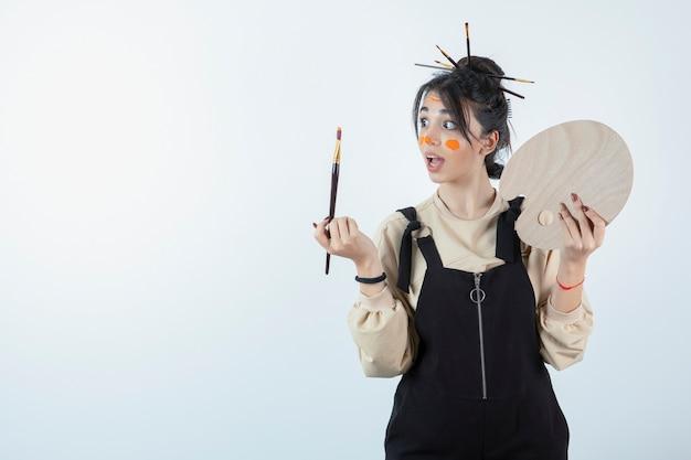 Portret młodej artystki pozuje z pomalowaną twarzą i trzyma drewnianą paletę.