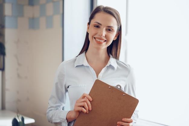 Portret młodej atrakcyjnej bizneswoman gospodarstwa schowka w biurze