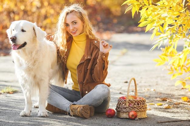 Portret młodej atrakcyjnej blond dziewczyny z psem. właściciel zwierzęcia. golden retriever i jego właściciel jesienią.