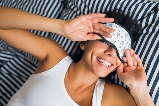 Portret młodej atrakcyjnej brunetki kobiety leżącej na łóżku w piżamie i masce do spania, uśmiechnięta w sypialni, radosne emocje, leniwa rano, pobudka, białe zęby