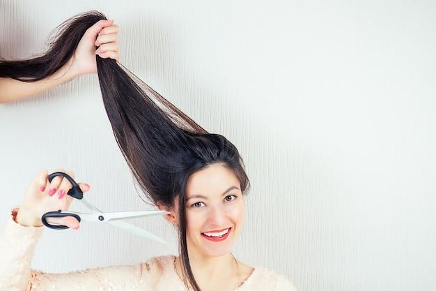 Portret młodej atrakcyjnej brunetki kobiety z długimi czarnymi włosami i nożyczkami do makijażu z strzyżeniem nożyczek w zakładzie fryzjerskim.