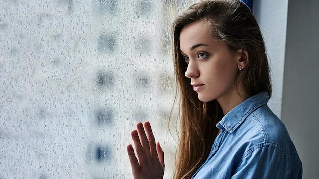 Portret młodej atrakcyjnej brunetki samotnej smutnej melancholijnej zadumanej kaukaskiej kobiety z długimi włosami stojącą samotnie w pobliżu okna z kroplami deszczu w deszczową jesienną pogodę