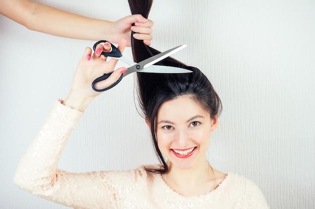 Portret młodej atrakcyjnej brunetki z długimi czarnymi włosami i makijażem w różowej sukience, nożyce z nożyczkami do fryzjera (zakład fryzjerski)