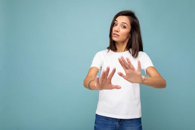 Portret młodej atrakcyjnej brunetki ze szczerymi emocjami na sobie dorywczo białą koszulkę dla