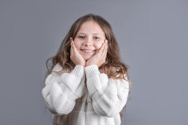 Portret młodej atrakcyjnej dziewczynki z długimi blond włosami płynące w białym swetrze, uśmiechając się na szarym tle studio. skopiuj miejsce.
