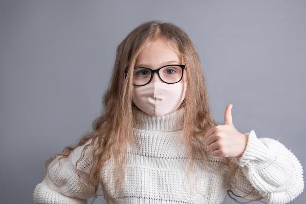 Portret młodej atrakcyjnej dziewczynki zw białym swetrze w medycznej masce ochronnej pokazuje kciuki do góry
