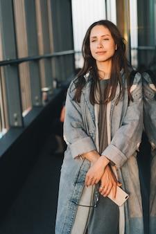 Portret młodej atrakcyjnej dziewczyny emocjonalnej ubranej w modny niebieski denimowy płaszcz