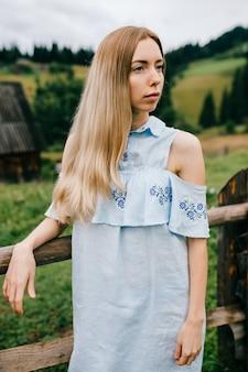 Portret młodej atrakcyjnej eleganckiej blondynki dziewczyny w niebieskiej sukience pozowanie na wsi