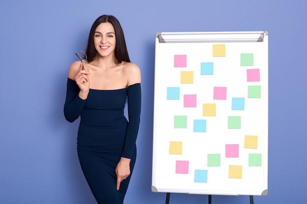 Portret młodej atrakcyjnej kobiety biznesu w ciemnoniebieskiej sukience stojącej na flip-chart w biurze.