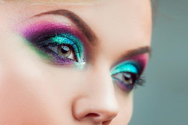 Portret młodej atrakcyjnej kobiety blondynka. zbliżenie makijażu, zielony i niebieski odcień