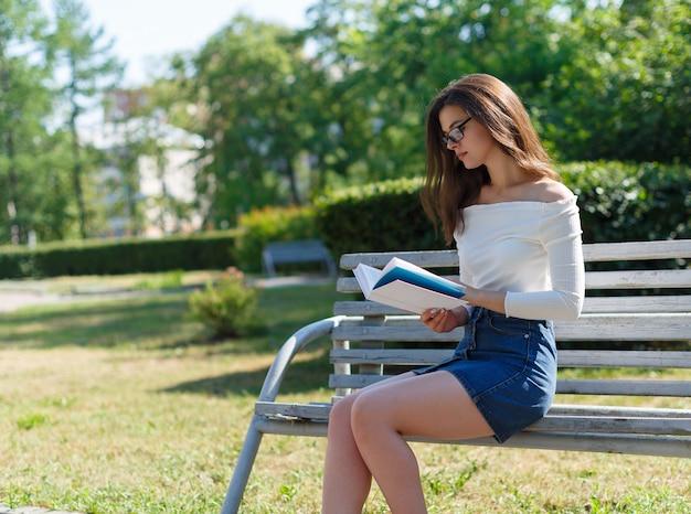 Portret młodej atrakcyjnej kobiety brunetka czytania książki, siedząc w letnim parku.