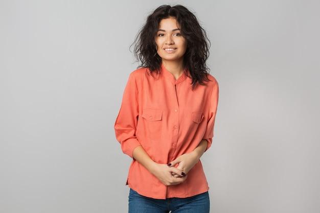 Portret młodej atrakcyjnej kobiety łacińskiej w pomarańczowej koszuli