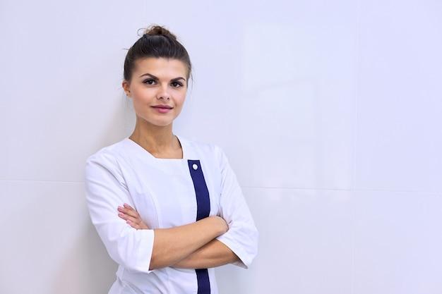 Portret młodej atrakcyjnej kobiety pewnie w mundurze medycznym z rękami skrzyżowanymi, tło kliniki światła ściany, miejsce. farmaceuta, pielęgniarka, kosmetolog, specjalista, naukowiec