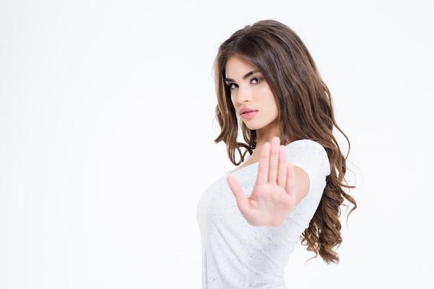 Portret młodej atrakcyjnej kobiety pokazującej znak stop z dłonią odizolowaną na białej ścianie