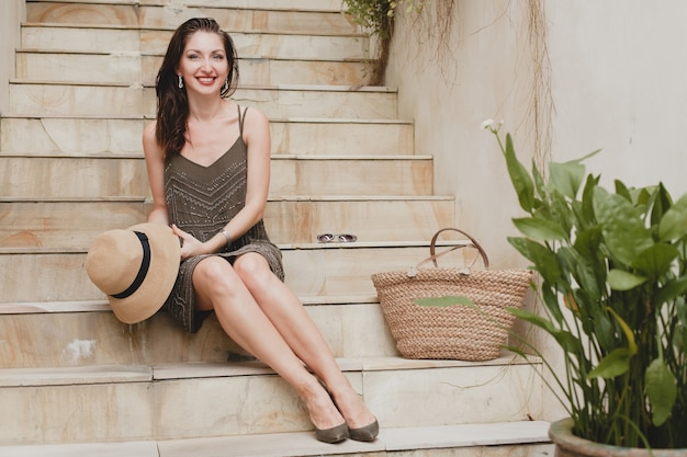 Portret młodej atrakcyjnej kobiety siedzącej na schodach w eleganckiej sukience trzymającej słomkowy kapelusz, letni styl, trend w modzie, wakacje, uśmiechnięta, szczupłe nogi, stylowe akcesoria, torba