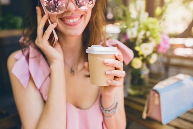 Portret młodej atrakcyjnej kobiety siedzącej w kawiarni, letni strój modowy, różowa bawełniana sukienka, okulary przeciwsłoneczne, uśmiechnięta, pije kawę, stylowe dodatki, modna odzież, rozmowa przez telefon