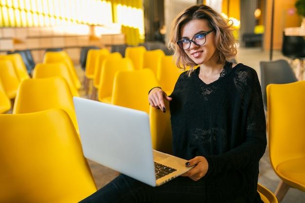 Portret młodej atrakcyjnej kobiety siedzącej w sali wykładowej, pracującej na laptopie, w okularach, w klasie, wielu żółtych krzesłach, edukacja studencka online, freelancer, stylowy