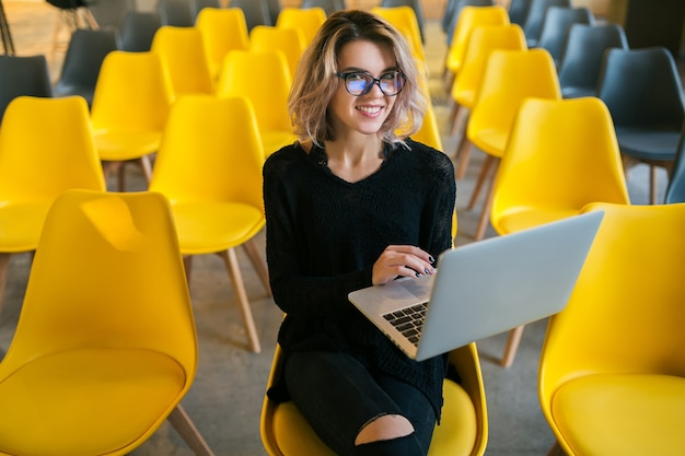 Portret młodej atrakcyjnej kobiety siedzącej w sali wykładowej, pracującej na laptopie w okularach