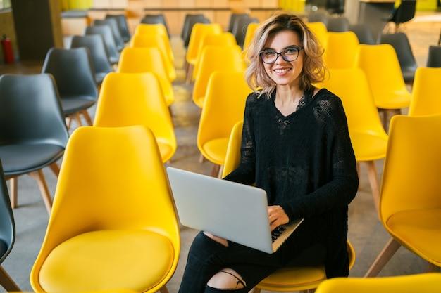 Portret młodej atrakcyjnej kobiety siedzącej w sali wykładowej pracy na laptopie w okularach, student uczenia się w klasie z wieloma żółtymi krzesłami