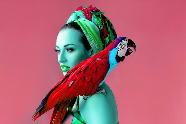Portret młodej atrakcyjnej kobiety w afrykańskim stylu z papugą ara na ramieniu