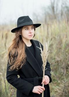 Portret młodej atrakcyjnej kobiety w czarnym płaszczu i kapeluszu