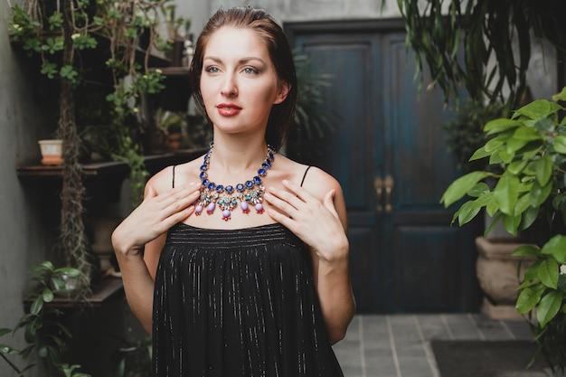 Portret młodej atrakcyjnej kobiety w eleganckiej czarnej sukience na sobie luksusową biżuterię z bogatym naszyjnikiem, styl letni, trend w modzie, wakacje, stylowe akcesoria, pozowanie na tropikalnej willi na bali