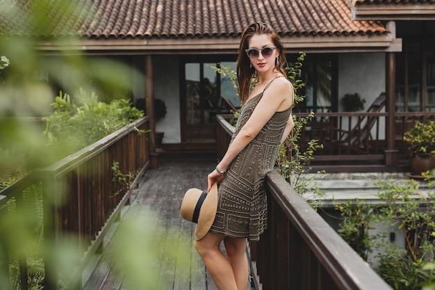 Portret młodej atrakcyjnej kobiety w eleganckiej sukience, słomkowym kapeluszu, letnim stylu, trendach w modzie, wakacje, uśmiechnięta, stylowe akcesoria, okulary przeciwsłoneczne, pozowanie na tropikalnej willi na bali