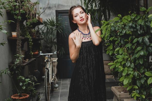 Portret młodej atrakcyjnej kobiety w stylowej czarnej sukience pozującej w tropikalnej willi, seksowny, elegancki styl lato, modne dodatki do naszyjników, uśmiechnięta, biżuteria, czysta naturalna skóra twarzy