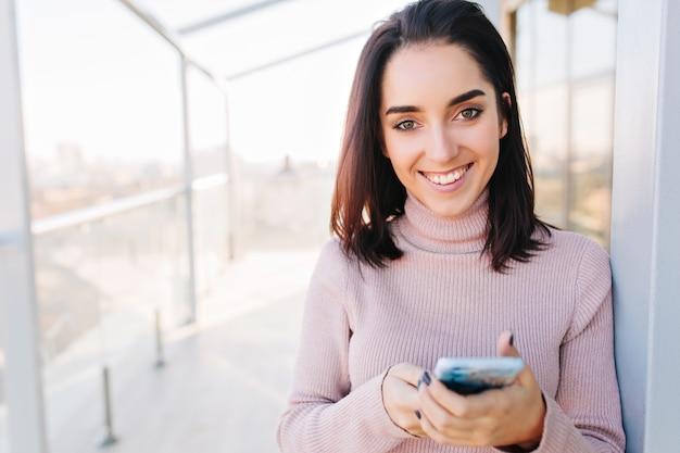 Portret młodej atrakcyjnej kobiety z brunetką uśmiechając się w słoneczny poranek na tarasie z widokiem na miasto. wyrażanie pozytywności, młoda kobieto.