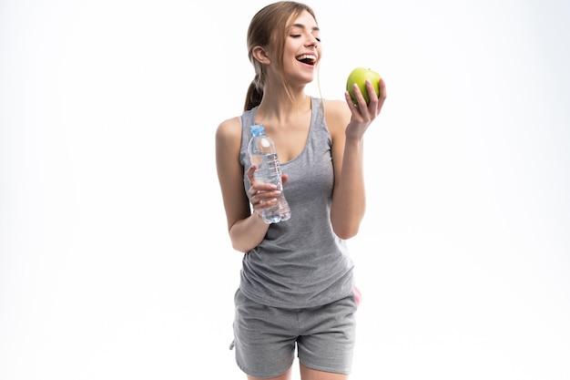 Portret młodej atrakcyjnej kobiety z zielonym jabłkiem i butelką
