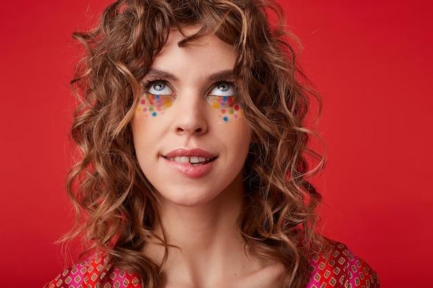 Portret młodej atrakcyjnej, kręconej kobiety z wielobarwnymi kropkami na twarzy, patrząc w górę w zamyśleniu i gryzącą dolną wargę, ubrana w pstrokaty wzorzysty top podczas pozowania