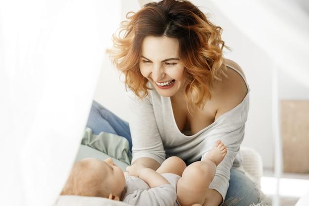 Portret młodej atrakcyjnej matki śmieje się i bawi się z noworodkiem w wygodnej, jasnej sypialni. ciepłe poranki z rodziną. szczęśliwe dzieciństwo.