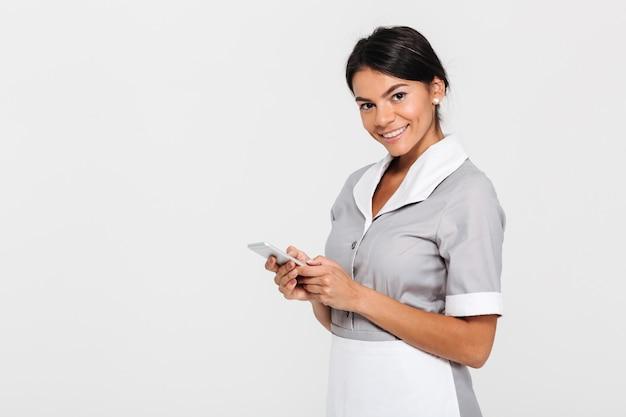 Portret młodej atrakcyjnej pokojówki w szarym mundurze posiadania telefonu komórkowego
