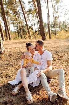 Portret młodej atrakcyjnej rodziny z małym synkiem, pozowanie w pięknym jesiennym lesie sosnowym w słoneczny dzień. przystojny mężczyzna i jego ładna brunetka żona
