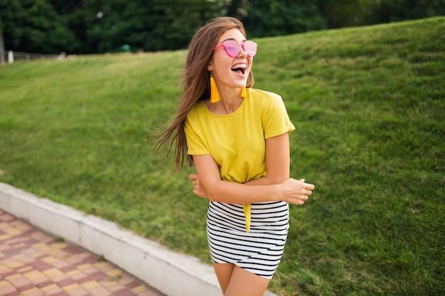 Portret młodej atrakcyjnej stylowej kobiety pozującej w parku miejskim, uśmiechnięta wesoła nastrój, pozytywna, ubrana w żółty top, mini spódniczka w paski, torebka, różowe okulary przeciwsłoneczne, letni trend w modzie