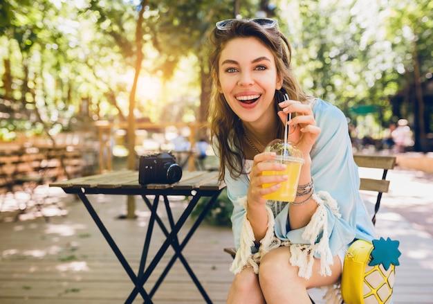 Portret młodej atrakcyjnej stylowej kobiety siedzącej w kawiarni, szczerze się uśmiechając, pijąc sok smoothy, zdrowy tryb życia, uliczny styl boho, modne dodatki, śmiejąc się, szczęśliwe emocje, słonecznie