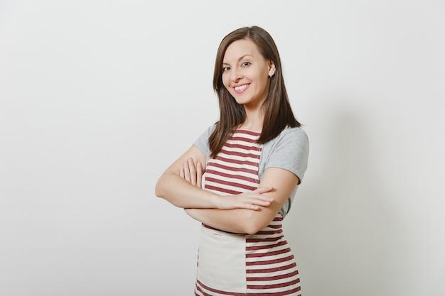Portret młodej atrakcyjnej uśmiechniętej brunetki kaukaskiej gospodyni domowej w pasiastym fartuchu na białym tle