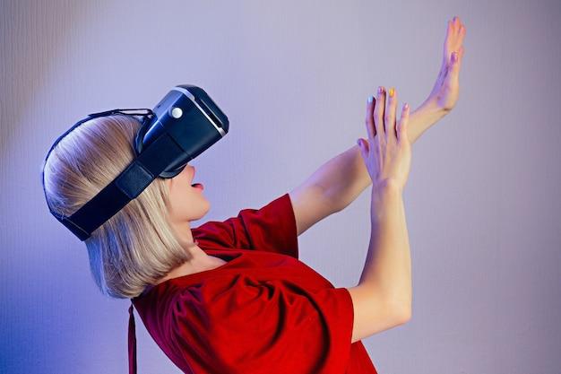 Portret młodej atrakcyjnej zdumionej kobiety o blond włosach w hełmie (okularach) wirtualnej rzeczywistości w szoku i zaskoczeniu