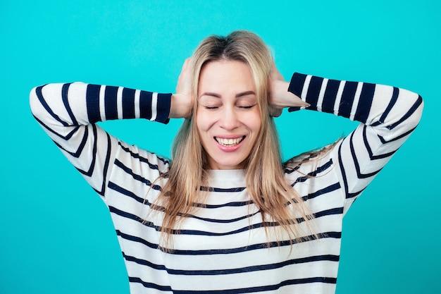 Portret młodej atrakcyjnej zszokowanej kobiety z blond włosami i ustami makijażu otwarte z zaskoczenia w studio na niebieskim tle. koncepcja wiadomości zdumionych i wow.