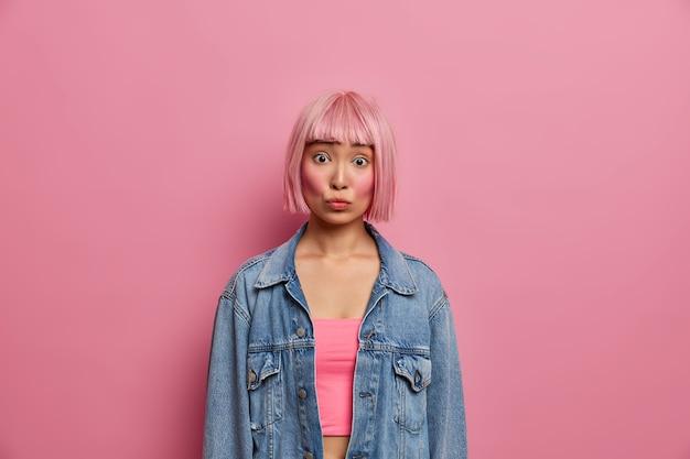 Portret młodej azjatki z modnymi różowymi włosami bob, zaskakuje zmartwioną miną, słyszy coś ekscytującego, ubrana w za dużą dżinsową kurtkę, pozuje w domu. modna dziewczyna ze wschodu
