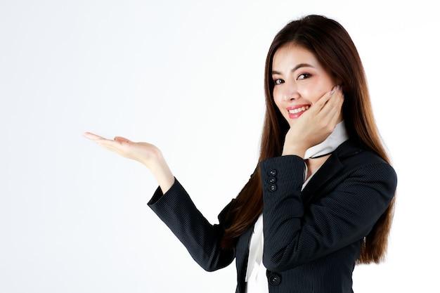 Portret młodej azjatyckiej bizneswoman w formalnym garniturze pozuje i pokazuje rękę w pustej przestrzeni