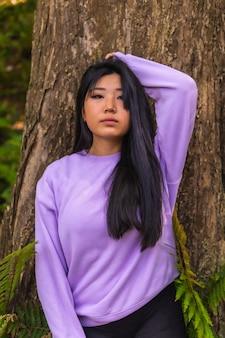 Portret młodej azjatyckiej brunetki w parku obok drzewa z różowym swetrem.