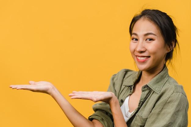 Portret młodej azjatyckiej damy uśmiechający się z radosnym wyrazem twarzy, pokazuje coś niesamowitego w pustej przestrzeni w swobodnym materiale na białym tle nad żółtą ścianą. koncepcja wyraz twarzy.