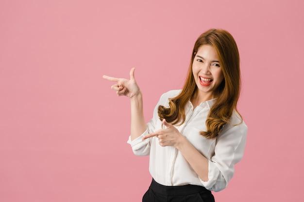 Portret młodej azjatyckiej damy uśmiechający się z radosnym wyrazem twarzy, pokazuje coś niesamowitego w pustej przestrzeni w swobodnym ubraniu i patrząc na kamerę na białym tle na różowym tle.